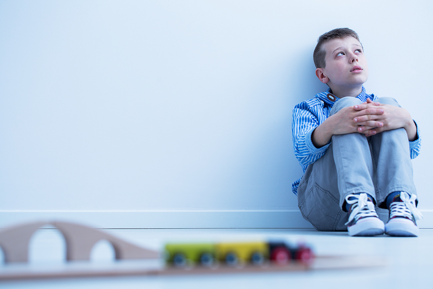 Boy in blue shirt sitting on floor and starring at wall, doesn't want to play with electric train